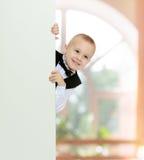 Pojken kikar ut bakifrån banret royaltyfri foto