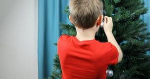 Pojken klär upp en grön julgran med en stor festlig boll arkivfilmer