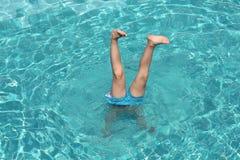 Pojken klibbar hans ben ut från vattnet av pölen Royaltyfri Foto