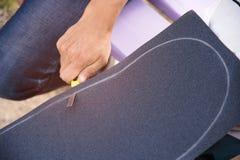 Pojken klipper griptapen på en skateboard Fotografering för Bildbyråer