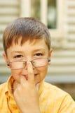 Pojken korrigerar exponeringsglas nära hus Royaltyfri Bild