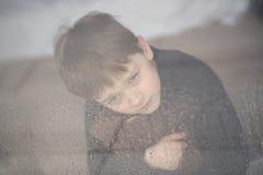 Pojken kramar hans nallebjörn Arkivbild