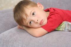 pojken lägger den SAD sofaen royaltyfria foton