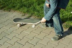 Pojken lär att rida en skateboard Arkivbilder