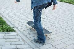 Pojken lär att rida en skateboard Arkivfoton