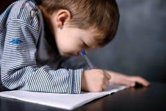Pojken lär att skriva royaltyfria foton