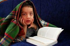 Pojken läser boken under filten royaltyfri fotografi