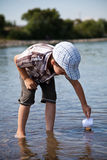 Pojken lanserar en liten segelbåt i floden Royaltyfri Foto