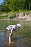 Pojken lanserar ett fartyg i floden Royaltyfria Bilder