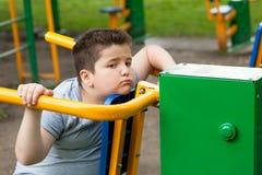 Pojken ledset, trött som är fet, konditioninstruktör, förlorar vikt, fetma, övervikt, övning, bantar Royaltyfri Fotografi