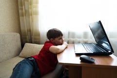 Pojken ligger i vardagsrummet på soffan och håller ögonen på en film på en bärbar dator royaltyfri fotografi