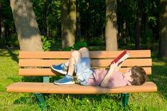Pojken ligger på en bänk i parkera och läsningen en bok Arkivfoton