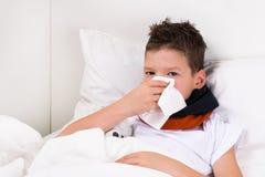 Pojken ligger på sängen och blåser hans näsa i en servett, snor efter sömn Arkivbild
