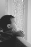 pojken little ser ut fönstret royaltyfria bilder