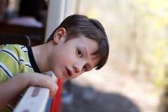 Pojken lutar ut från fönster royaltyfri bild