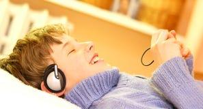 pojken lyssnar musik till Royaltyfri Bild