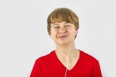 Pojken lyssnar till musik med hörlurar Arkivbilder
