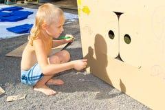 Pojken målar en kartong royaltyfri foto