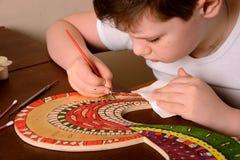 Pojken målar färgerna av trät Fotografering för Bildbyråer