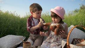 Pojken matar flickan med bageriprodukten, gulliga små ungar som in delar bröd, produkter i picknickbaske, barn som har gyckel arkivfilmer