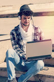 Pojken med bärbara datorn i stads- miljö med ett filter applicerade insta Arkivbild