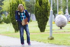 Pojken med böcker i hans händer går till skolan utomhus- Arkivfoto