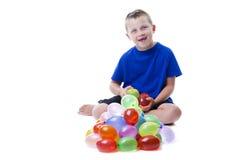 Pojken med bevattnar ballonger Royaltyfri Bild