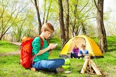 Pojken med den röda ryggsäcken skriver anteckningsboken på att campa Royaltyfria Bilder