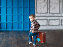 Pojken med en resväska i det stora rummet Arkivfoto