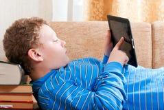 Pojken med en tabletdator är på bokar Arkivbild