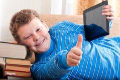 Pojken med en tabletdator är på bokar Arkivfoton
