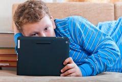 Pojken med en tabletdator är på bokar Royaltyfria Bilder
