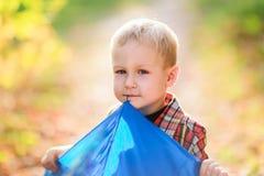 Pojken med ett blått paraply Arkivfoto