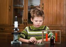 Pojken med ett mikroskop och färgrika flaskor Royaltyfri Foto
