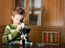 Pojken med ett mikroskop och färgrika flaskor Arkivfoton