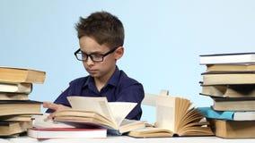 Pojken med exponeringsglas sitter på en tabell, och spännande söker efter det background card congratulation invitation lager videofilmer