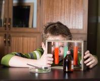 Pojken med färgrika flaskor Arkivbild