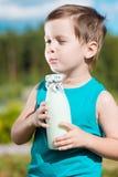 Pojken med flaskan av mjölkar säger mooooo Royaltyfri Bild