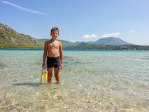 Pojken med flipper i havet på en härlig bakgrund arkivbild