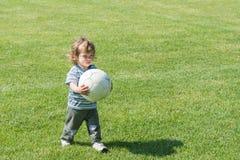 Pojken med fotboll klumpa ihop sig Arkivbilder