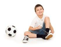 Pojken med fotboll klumpa ihop sig Arkivfoton
