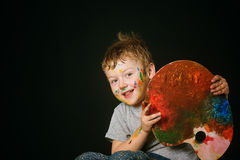 Pojken med händer målade i ljusa färger, med paletten i hand Royaltyfri Bild