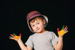 Pojken med händer målade i ljusa färger, med paletten i hand Royaltyfri Fotografi