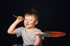 Pojken med händer målade i ljusa färger, med paletten i hand Arkivfoton