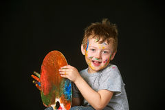 Pojken med händer målade i ljusa färger, med paletten i hand Arkivbilder