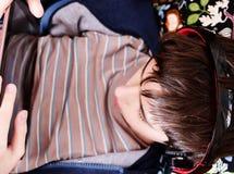 Pojken med hörlurar ser på minnestavlan Arkivbilder