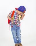 Pojken med hatten äter frukt i en rolig väg arkivfoton