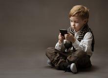 Pojken med mobil ringer arkivbild