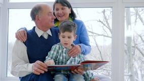 Pojken med morfadern och mormodern läste boken, och hålla ögonen på föreställer hemma arkivfilmer