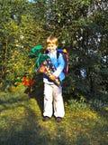 Pojken med pappkotten fyllde med sötsaker och gåvor på hans första dag av skolan Royaltyfria Bilder